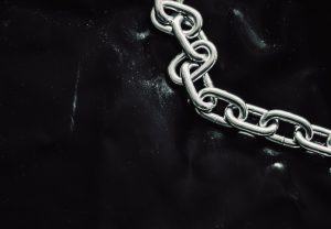 Silver chain link on black background, cybersecurity weakest link concept